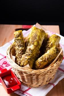 Продовольственная концепция домашнего песто хлебные палочки в корзине для хлеба на деревянной доске с копией пространства