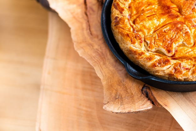 Food concept homemade pork pie or meat pie in cast iron skillet and stone plate on wooden background