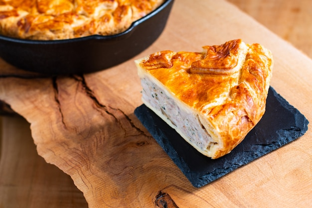 Food concept homemade pork pie or meat pie on stone plate and cast iron skillet on wooden background