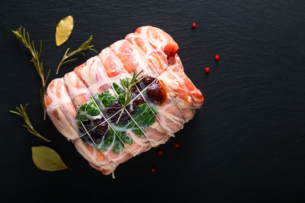 Food concept homemade raw stuffed pork tenderloin on black slate stone plate with copy space