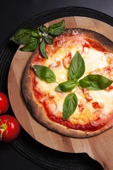 食品のコンセプト木の板に自家製トルティーヤマルゲリータピザ