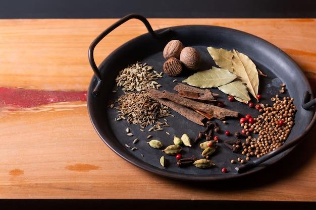 Пищевые ингредиенты для специй масала карри в старинном железном подносе на дереве с копией пространства