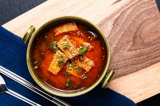 복사 공간이 있는 나무 판자에 있는 음식 개념 한국 매운 두부 수프