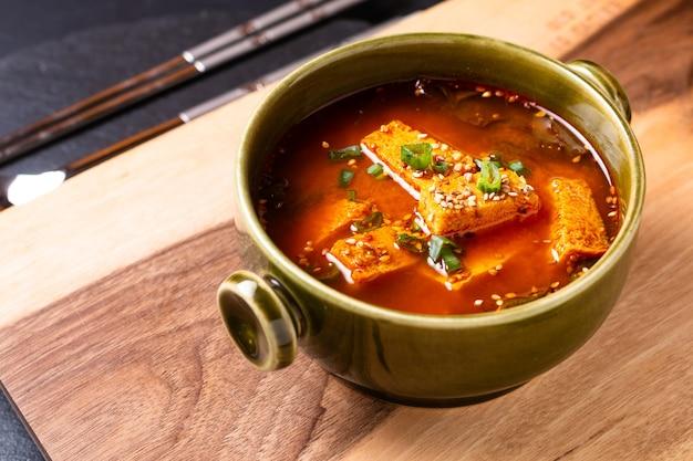 Концепция питания корейский острый суп с тофу на деревянной доске с копией пространства