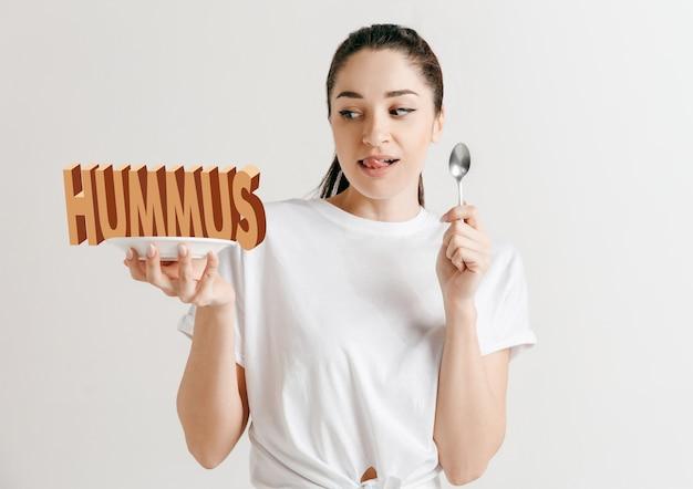 Концепция питания. модель держит тарелку с буквами хумуса