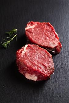 Концепция еды органическое филе миньон стейк сырая говядина на черной грифельной доске с копией пространства