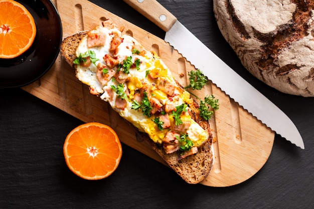 Food concept organic french sourdough toasted with eggs and ham on wooden cutting board