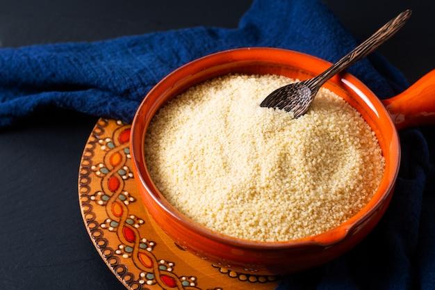 Food concept organic raw couscous in orange bowl