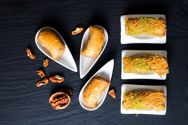 Food concept oriental arab dessert baklava walnuts and rolled kanafeh on black slate board