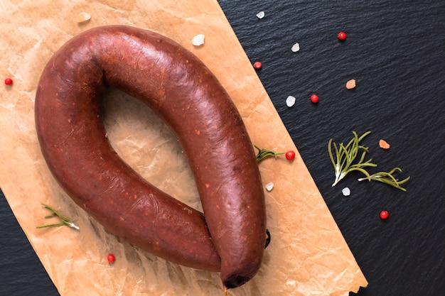 Концепция питания сырая кровь пудинг черные колбасы на черном сланцевом камне