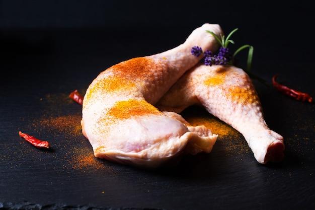コピースペースのある黒いスレートの石板にスパイスが入ったフードコンセプトの生の鶏肉の四分の一