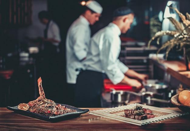 Концепция питания. готовое блюдо из свиных ребрышек на гриле и стейк из говядины с зеленью. готов к подаче. готовые к употреблению. два шеф-повара, работающие на заднем плане интерьера современной профессиональной кухни ресторана
