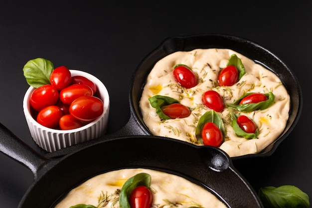 Food concept rising dough for vegan homemade organic focaccia in skillet iron pan on black background with copy space