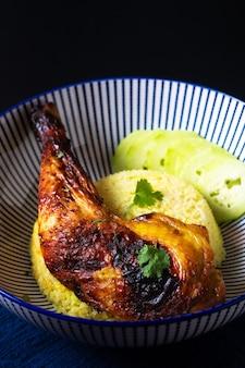 Продовольственная концепция жареный цыпленок qaurter и рис с куркумой на черном фоне с копией пространства