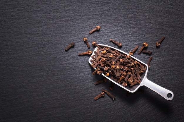 Концепция еды специи гвоздики на черном сланцевом камне