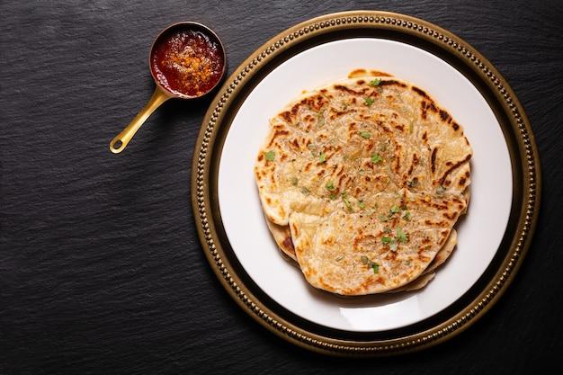 음식 개념 자리 초점 집에서 만든 paratha, parotta 또는 porotta는 검은 색 바탕에 flatbread를 계층화했습니다.