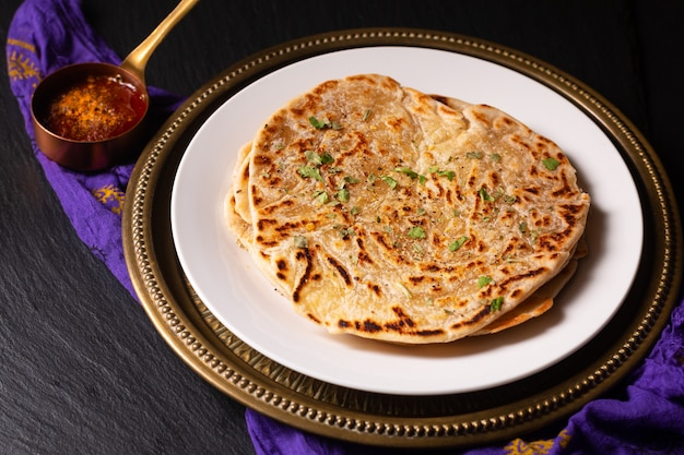 Food concept spot focus homemade paratha, parotta or porotta layered flatbread  on black background