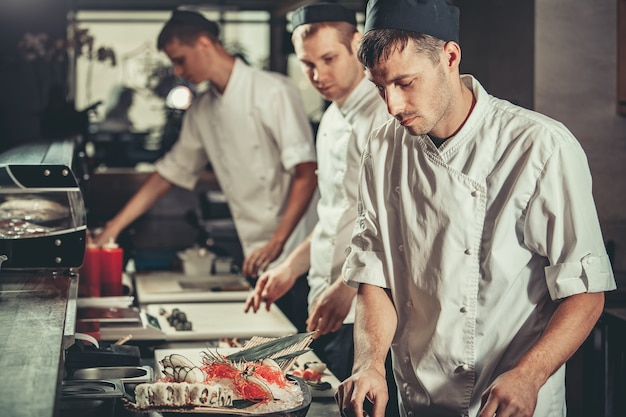 Food concept three young chefs in white uniform decorate ready dish in restaurant they are working