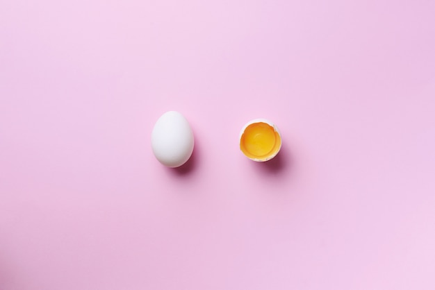 Food concept with broken egg and whole one on pink backgroun