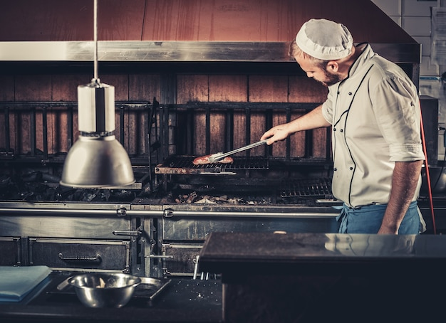 食品のコンセプト。白い制服を着た若いシェフが焙煎の程度を監視し、モダンなレストランのキッチンのインテリアで鉗子で肉を回します。バーベキューオーブンで伝統的なビーフステーキを準備する
