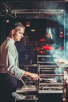 白い制服を着た若いハンサムなシェフが焙煎の程度を監視し、肉を回す食品コンセプト