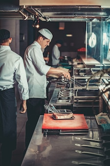 음식 컨셉은 흰색 유니폼을 입은 젊고 잘생긴 요리사들이 석탄을 켜고 온도를 모니터링합니다.