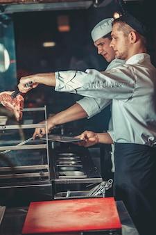 Концепция питания. молодые красивые повара в белых мундирах разжигают угли и кладут сырое маринованное мясо на решетку в интерьере кухни ресторана. готовим традиционный стейк из говядины в печи для барбекю.
