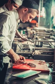 Концепция питания. молодой серьезный шеф-повар в белой униформе вырезал мясное блюдо из говяжьего стейка на красной разделочной доске в интерьере современной профессиональной кухни ресторана. готов к подаче. готовые к употреблению