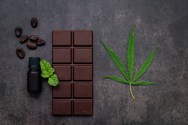 Food conceptual image of  cannabis leaf  with dark chocolate and fork on dark concrete background.