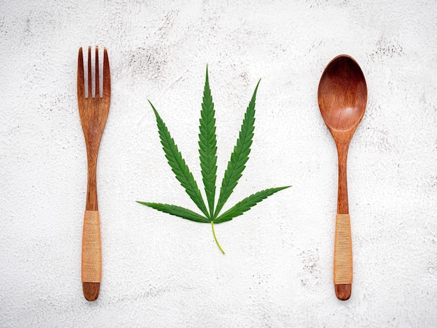 Food conceptual image of a cannabis leaf  with spoon and fork on white concrete.