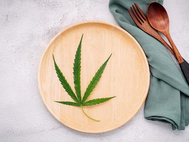 Еда концептуальное изображение листа конопли с ложкой и вилкой на белом бетоне.