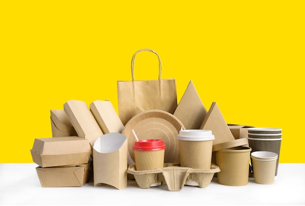 노란색 배경에 친환경 종이로 만든 식품 용기.