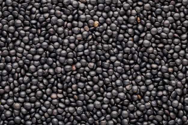 Food and cookery background of healthy dried  black lentils