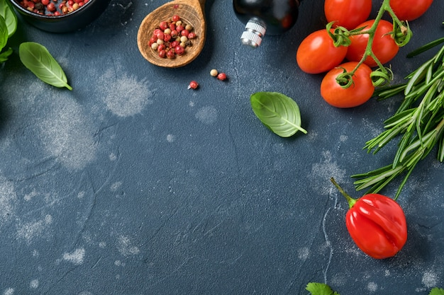 食品調理の背景。新鮮なローズマリー、コリアンダー、バジル、チェリー トマト、ピーマン、オリーブ オイル、スパイス ハーブ、野菜を黒い石板のテーブルに並べます。食材のトップ ビュー。