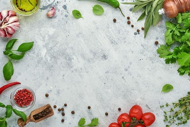 음식 요리 배경입니다. 밝은 회색 슬레이트 테이블에 신선한 사프란, 마늘, 실란트로, 바질, 체리 토마토, 고추, 올리브 오일, 향신료 허브와 야채. 음식 재료 상위 뷰입니다.