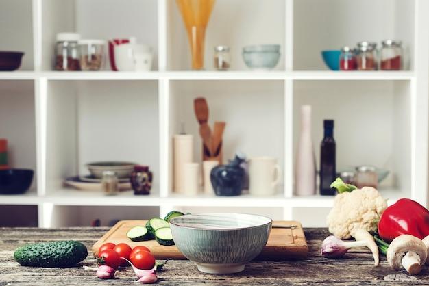 野菜と料理の背景。キッチンカウンターでベジタリアン料理の食材。ぼやけたキッチンの背景。健康食品とダイエットのコンセプト。木の板の野菜。