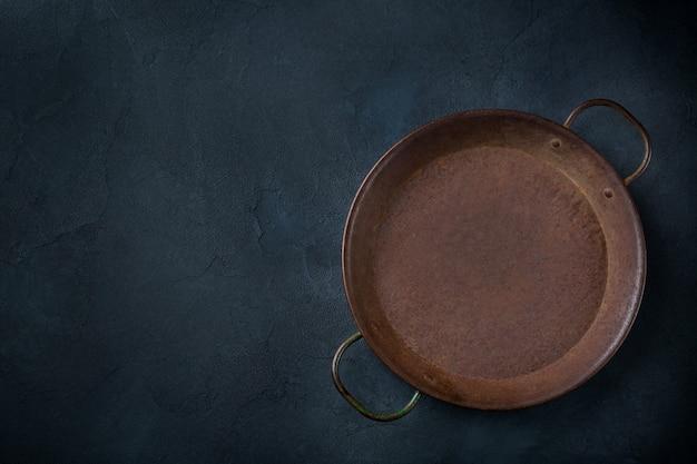 Концепция приготовления пищи. пустая чугунная сковорода на темном фоне. плоская планировка, вид сверху, копия пространства