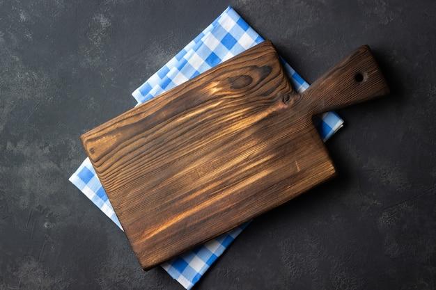 Концепция приготовления пищи. винтажная деревянная кухонная доска над салфеткой на темном каменном фоне.