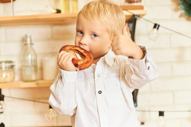 Concetto di cibo, cucina, pasticceria e panetteria. ritratto del ragazzino dagli occhi blu bello godendo bagel appena sfornato durante la colazione in cucina, gesticolando, facendo il pollice in alto segno