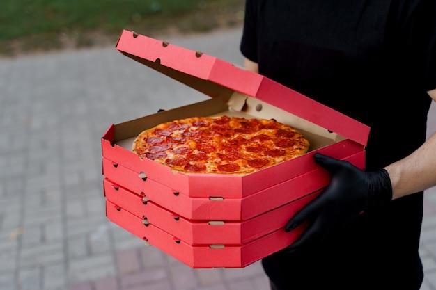 피자와 함께 검은 의료 장갑에 음식 택배