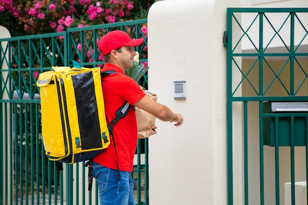 Food courier in uniform with isothermal backpack and paper package ringing doorbell. shipping or delivery service concept