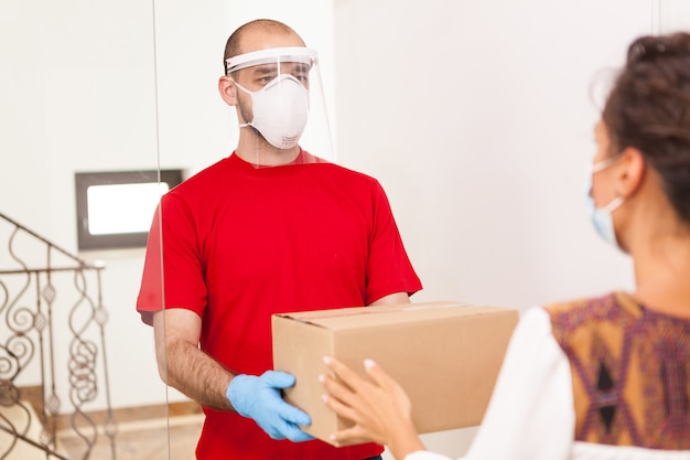 Food courier with protection mask delivering package to female costuomer.