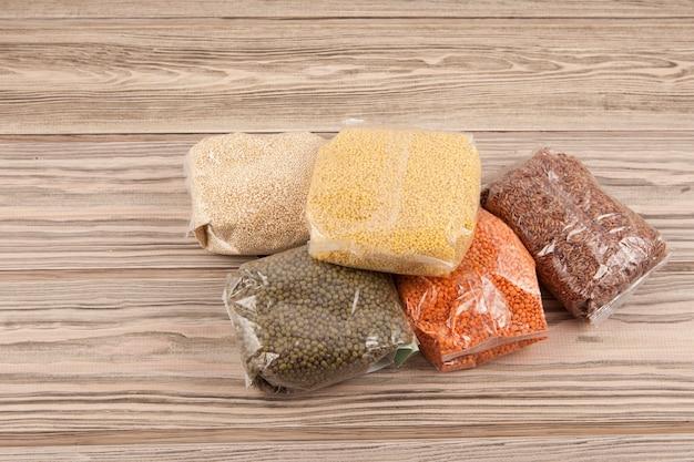 식량 위기. 자가 격리 기간 동안 택배에 대한 인도 주의적 지원. 곡물은 장기 저장 제품입니다. 나무 테이블에 음식 가방입니다.