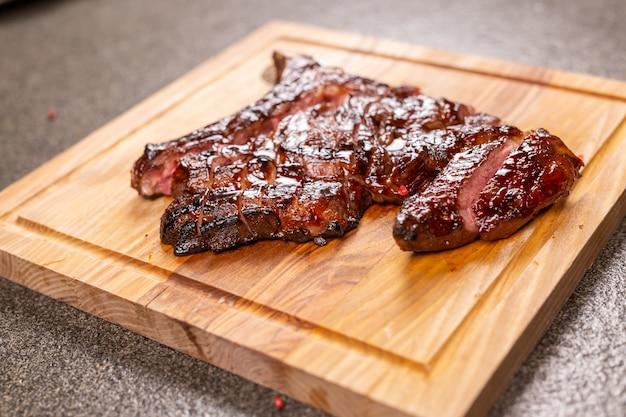 食べ物、美味しさ、クラフトのコンセプト-木製の机の上で馬肉ステーキを切る