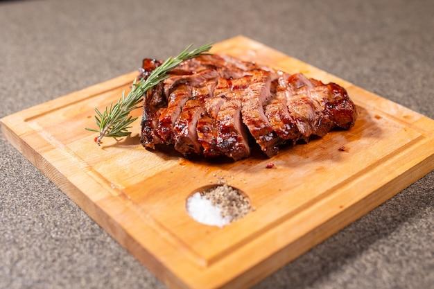 食べ物、美味しくてクラフトのコンセプト-木製の机の上で馬肉ステーキを切る