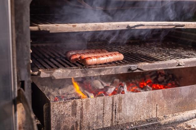 食べ物、美味しくてクラフトのコンセプト-燃えるようなグリルで焼いたソーセージ