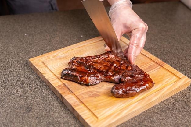음식, 맛있고 공예품 개념 - 말고기 스테이크를 자르는 남자.
