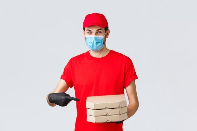 Доставка еды, приложение, онлайн-магазин, бесконтактные покупки и концепция covid-19. веселый курьер в красной форме, маске для лица и перчатках, указывая пальцем на коробки для пиццы, доставить на дом клиента