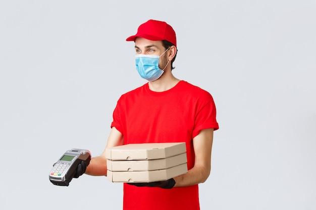 Доставка еды, приложение, онлайн-магазин, бесконтактные покупки и концепция covid-19. приятный доставщик в красной форме, перчатках и маске, отдавая заказ клиенту с pos-терминалом, доставляет пиццу
