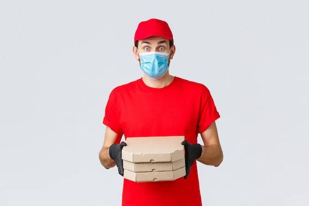 フードデリバリー、アプリケーション、オンライン食料品店、非接触型ショッピング、covid-19コンセプト。赤いユニフォーム、フェイスマスク、手袋を身に着けた驚きの宅配便、印象に残っているように見える、顧客にピザを持ってくる、箱を持って